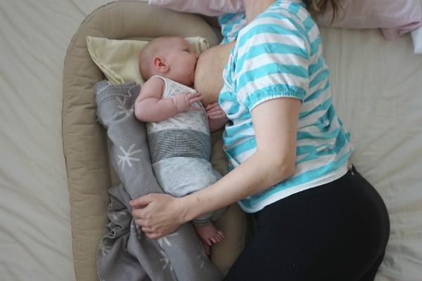 Socialstyrelsens sovråd för bebisar. Mamma ammar bebis i babynest, liggande.