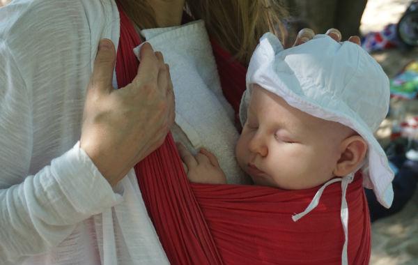 Bära barn i sommarvärmen. En liten handduk läggs mellan bebis och bärare, på bärarens bröstkorg.