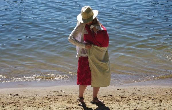 Bära barn i sommarvärmen. Bebis i bärsjal på strand har en liten tunn filt över benen.