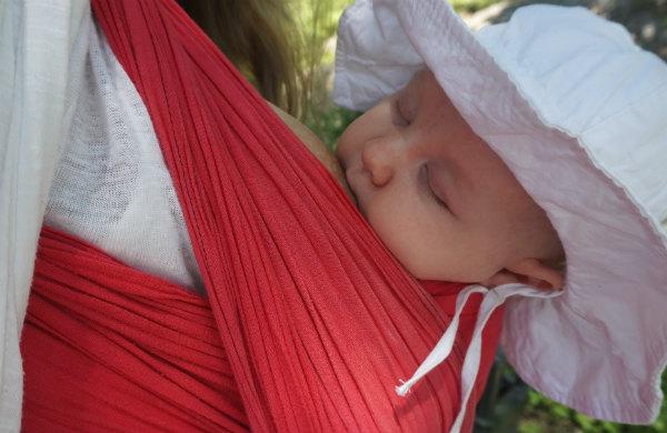 Bära barn i sommarvärmen. Bebis i vid vit solhatt ammar i röd bärsjal.