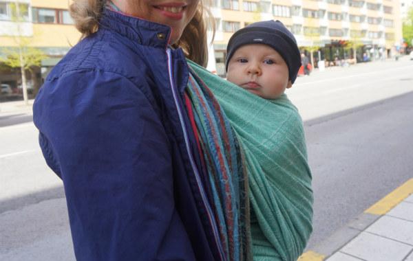 Bära en nyfödd bebis i bärsjal. Bebis i grön bärsjal, utomhus.