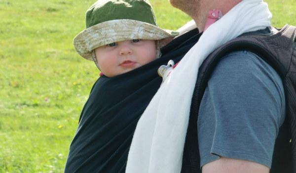 Varför bära barn. Bebis bärs i svart bärsjal på pappas bröst, utomhus, sommar.