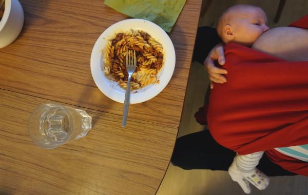Amma i trikåsjal, video. Bebis ligger i röd sjal vid matbord, pastaskål på bordet.