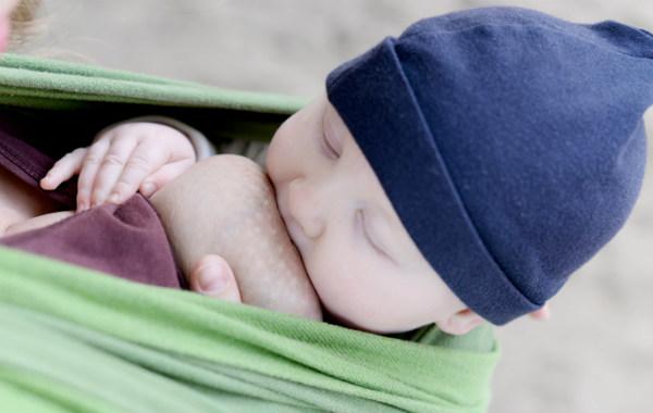 Amningsstrejk. Bebis ammar i grön bärsjal, utomhus sittande upprätt.