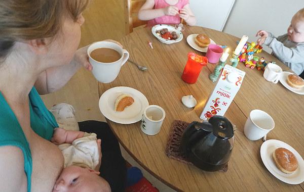 Amningsstrejk. Måltid vid runt bord med tre barn, ett av dem ammar i famnen hos kvinna som håller i kaffekopp.