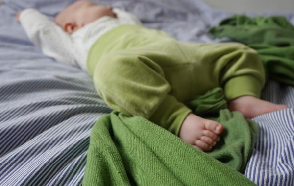 Amningsstrejk. Bebis sover på rygg på säng. Bärsjal i förgrunden.