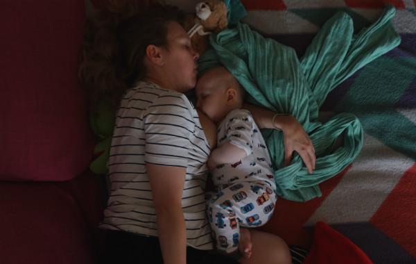 Amningsstrejk. Liggamning i mörkt rum, bebis ligger på mammans arm.