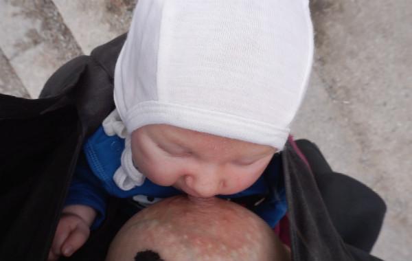 Amma liten bebis i bärsele. Utomhus, vår, bebis ska precis ta bröstet sedd ovanifrån.