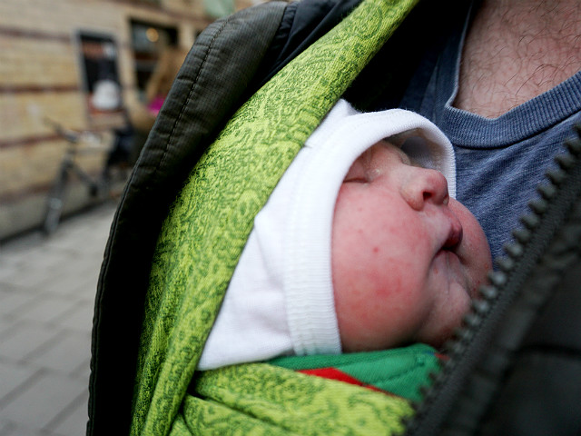 Stressen i förlossningsvården, amning. Nyfödd bebis i grön bärsjal på sin pappas bröstkorg, utomhus.