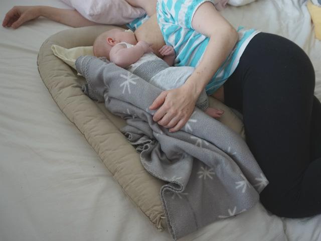 Liggamning, mamma och bebis ligger på sidan i säng. Bebis ligger i ett babynest och ammar. Mamman håller en hand bakom barnet, som stöd.
