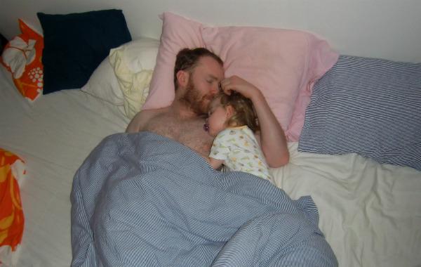 Personligt om samsovning. Ettåring sover på pappas arm i sängen. Pappa snusar på barnets huvud.