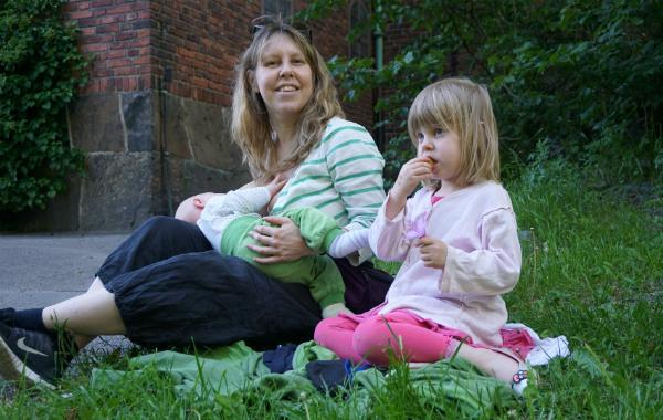 Amma ute. Mamma ammar bebis utanför kyrka, på gräs. Större barn sitter i gräset bredvid.