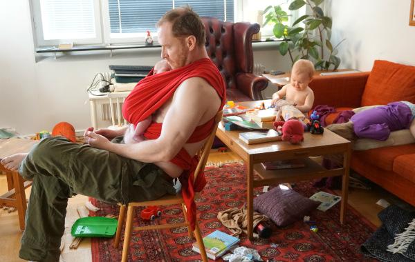 Amningsdagbok del två. Pappa har bebis i bärsjal, sitter på stol i stökigt rum. Ett äldre syskon leker.