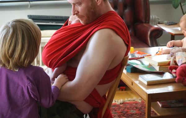 Amningsdagbok del två. Nyfödd i röd bärsjal på sin pappa.
