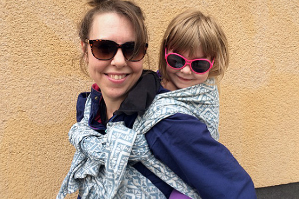 Större barn i bärsjal på mammans rygg, utomhus.