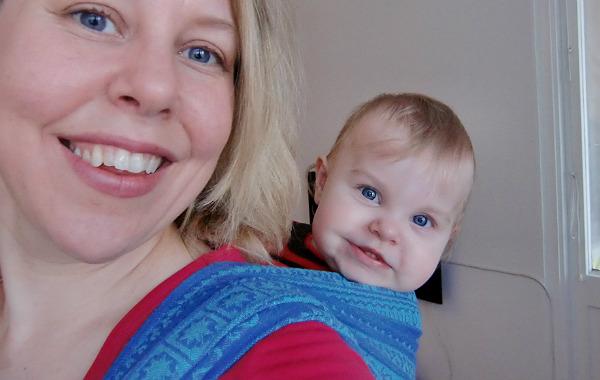 Bebis i bärsjal på mammans rygg.