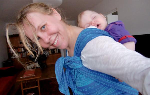 Bära barn på ryggen. Bebis sover i bärsjal på mammans rygg, vardagsrum.