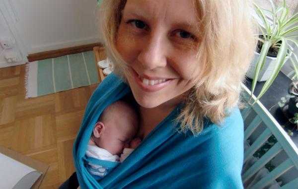 Tips till blivande förälder. Kvinna bär nyfödd bebis i blågrön bärsjal, inomhus.