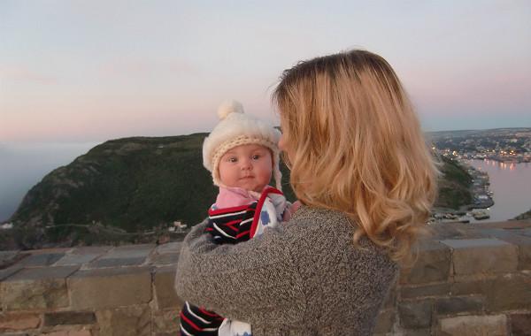 Mest förvirrande sakerna med amning. Bebis i mammas famn högt uppe på ett berg, gryning. Hamn i bakgrunden.