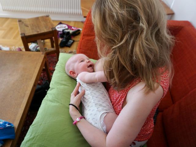 Amning och ont i ryggen. Bebis tittar på mamma och skrattar, har nyss ammat liggande på kudde i soffa.