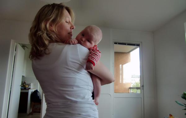 Mest förvirrande sakerna med amning. Mamma har liten trött bebis över axeln, står upp inomhus.