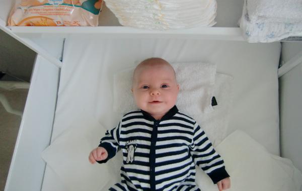 Mest förvirrande sakerna med amning. Glad bebis på skötbord, i randig dräkt.