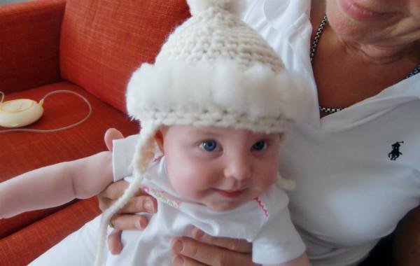 Mest förvirrande sakerna med amning. Bebis i vintermössa i mormors knä inomhus på soffa, bröstmjölkspump i bakgrunden.