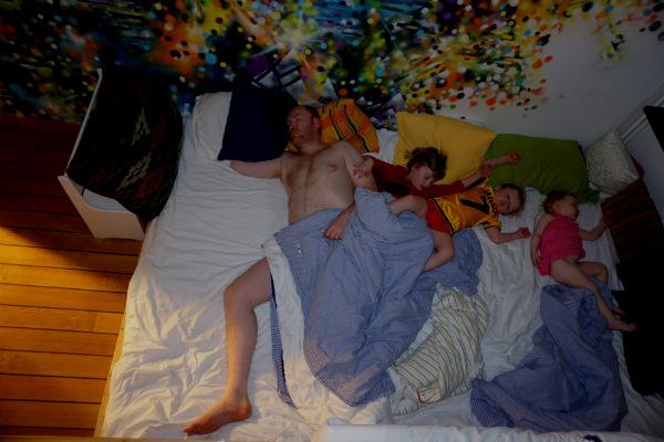 Säng för samsovning. En vuxen och tre barn sover i säng.