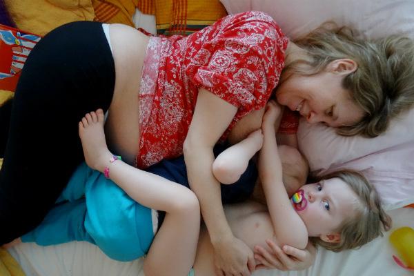 Tandemamning. Amning under graviditet, höggravid mamma ammar litet barn i sängen. Större syskon ligger intill och kramar om de båda.
