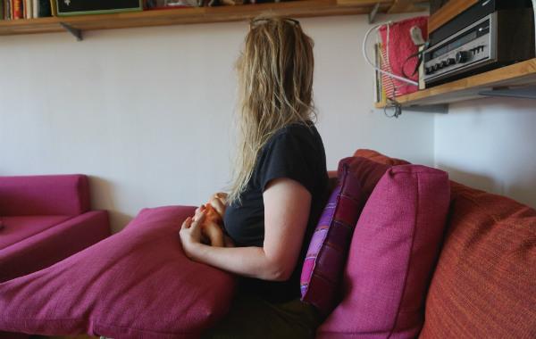 Amning och ont i ryggen. Amning med docka i soffa, sittande. Kuddar i ryggen på den ammande.