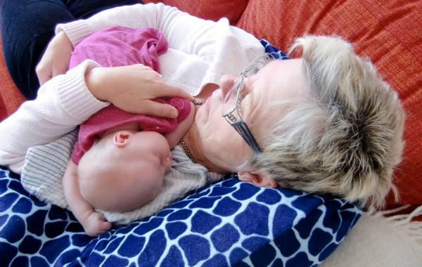 Tilläggsmata mindre, ge mindre ersättning. Mormor med bebis. Båda ser ut att sova, på soffa.