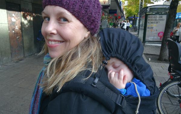 Nytt barn, ny amning. Mamma bär sovande barn på ryggen i bärsele, höst, utomhus.