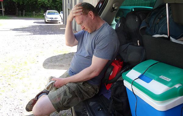 Tandemamning. Trött man tar sig för pannan sittande vid bagageutrymmet i bil, sommar.