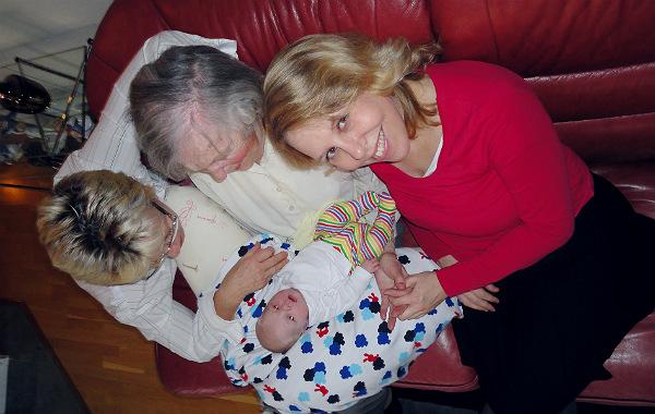 Tilläggsmata mindre, ge mindre ersättning. Nyfödd bebis. Mormor och gammelmormor tittar på bebisen, mamman tittar in i kameran.