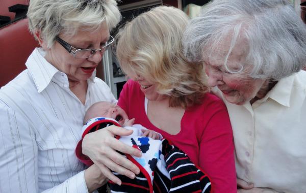 Tilläggsmata mindre, ge mindre ersättning. Nyfödd bebis i famnen på mamma. Mormor och gammelmormor tittar på bebisen.