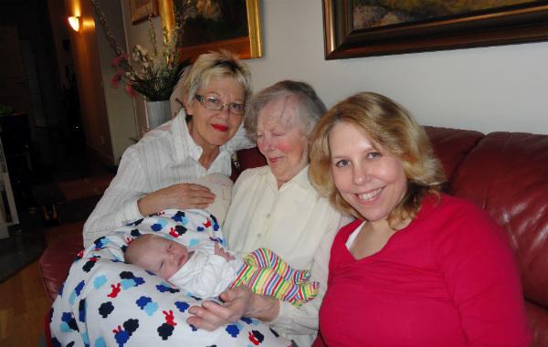 Tilläggsmata mindre, ge mindre ersättning. Mormor, gammelmormor, mamma och bebis i soffa.