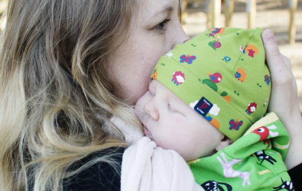 Kvinna har liten bebis mot sin axel, utomhus.