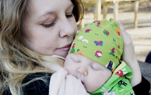 Tilläggsmata mindre, ge mindre ersättning. Liten bebis sover på mammans axel, utomhus.