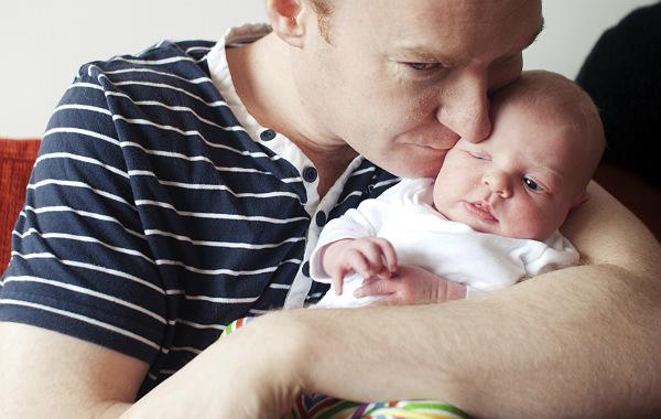 Tilläggsmata mindre, ge mindre ersättning. Pappa pussar nyfödd bebis, inomhus.