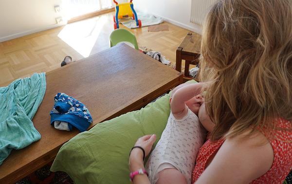 Mest förvirrande sakerna med amning. Bebis vid mammas bröst i soffa, stökigt vardagsrum.