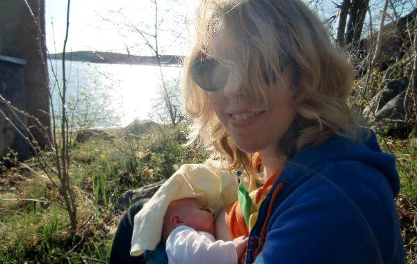 Mest förvirrande sakerna med amning. Liten bebis ammar utomhus, vår/sommar. Sjö i bakgrunden, solsken.