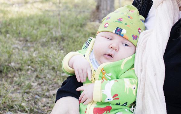 Mest förvirrande sakerna med amning. Liten bebis utomhus, vår, grön mössa och overall.