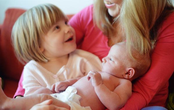 Mest förvirrande sakerna med amning. Inomhus, nyfödd bebis i famnen på mamma, större syskon sitter också i famnen och tittar leende upp mot sin mamma.