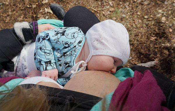 Mest förvirrande sakerna med amning. Liten bebis ammar i skogen, vår/sommar.