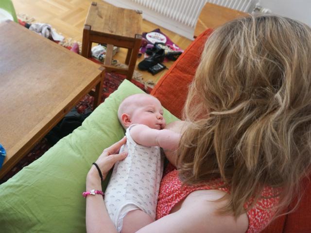 Bebisen vill bara amma på ena bröstet. Bebis ammar på kudde i soffa.