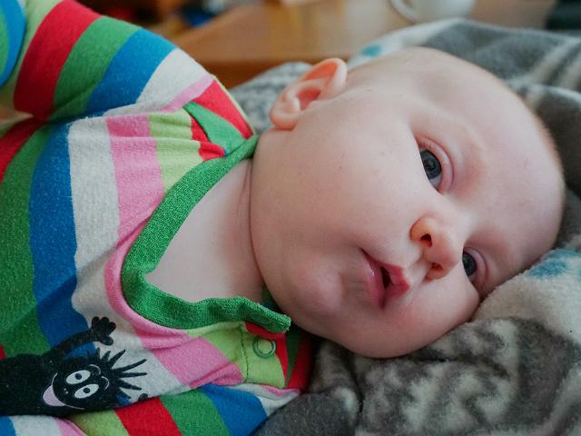 Mest förvirrande sakerna med amning. Liten bebis ligger på filt, tittar in i kameran.