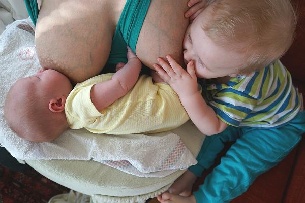 Tandemamning. Bebis och större syskon ammar samtidigt. Bebisen ligger ned och det större syskonet sitter upp.