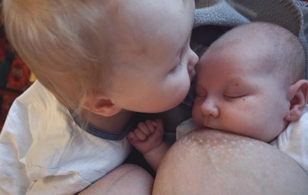 Tandemamning. Större syskon pussar mindre, mindre syskonet ammar.