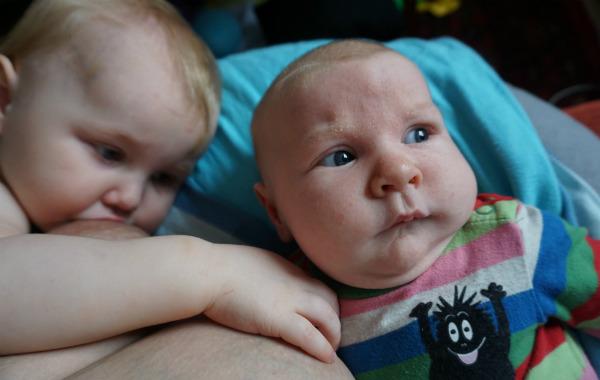 Tandemamning. Större syskon vaktar båda brösten, bebisen ser ut som om han är snuvad på konfekten.