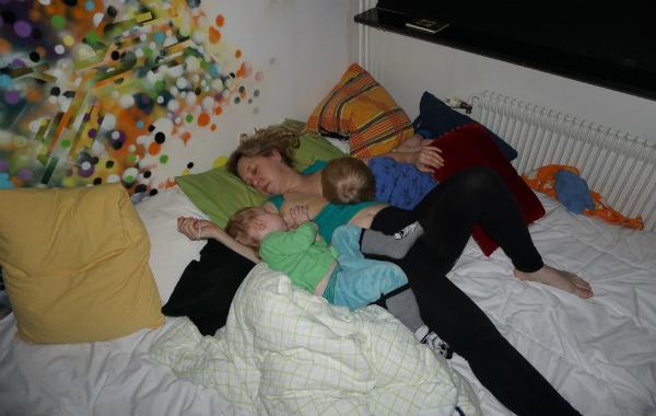 Tandemamning. Mamma har somnat på rygg i säng, tillsammans med två barn som har somnat vid hennes bröst.
